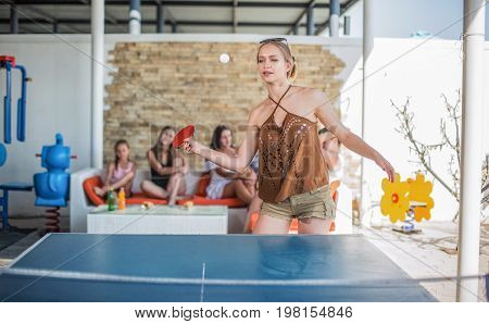 A gorgeous female plays ping-pong on the sunny entertaining center background. The competitive and successful young woman is playing table tennis. The smiling lady on an active summer holiday.