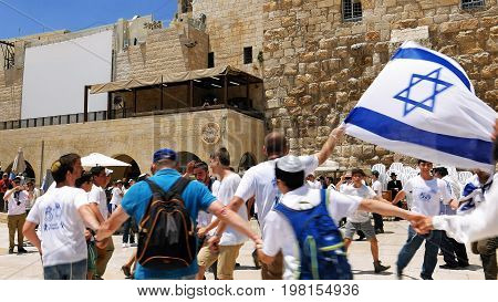 Jerusalem, Israel - May 25, 2017: Jews dancing in a round with flag celebrating the Jerusalem Day at Western Wall - Wailing Wall or Kotel - the most sacred place for all jews and jewish in the world.