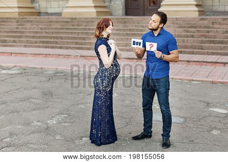 Funny image. Couple expecting a baby: man holds a sign saying