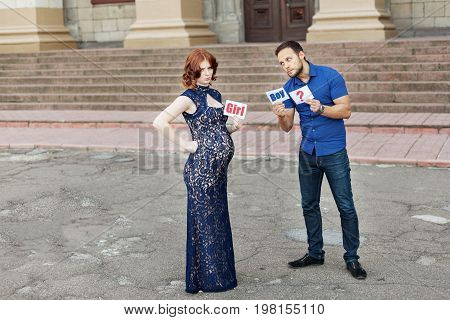 Funny image. Couple expecting a baby girl: man holds a sign saying