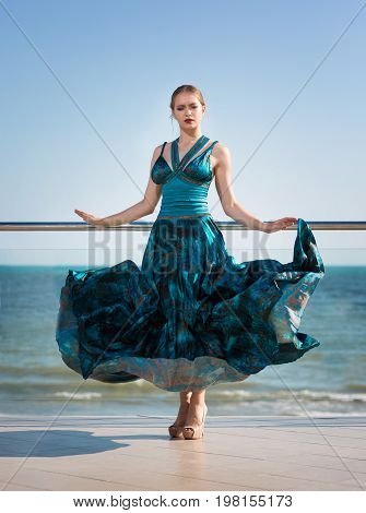 An elegant female in a sophisticated dress on a light blue ocean background. A glamorous girl in a beautiful dress on a hotel balcony. A thoughtful and feminine young woman posing near the sea.