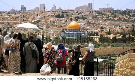 Jerusalem, Israel - May 25, 2017: The Christian orthodox guide shows the Jerusalem Old City view to the pilgrims and tourists from the Mount of Olives. Famous Holy Land place and fantastic city view.