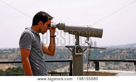 Jerusalem, Israel - May 25, 2017: Tourist looks in binoculars tower viewer at the city view. Tower viewer is popular device to look at the city details. Tourists love to use binoculars.