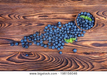 Top view of bright juicy blueberries in a wooden wicker basket. Fresh dark blue berries on a wooden background. Ripe fruits and berries in a brown crate. Natural summer berries for dessert. Copy space