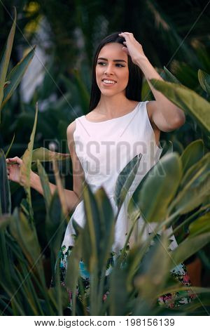 A beautiful girl with dark brown hair in the park. A positive female in a tropical forest. A sexy young woman is pretty charming smiling on the natural bright green leaves background. Natural concept.