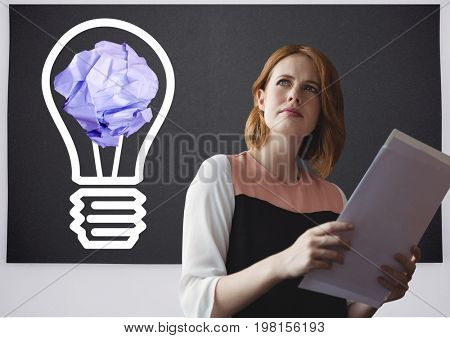 Digital composite of Woman holding tablet standing next to light bulb with crumpled paper ball in front of blackboard