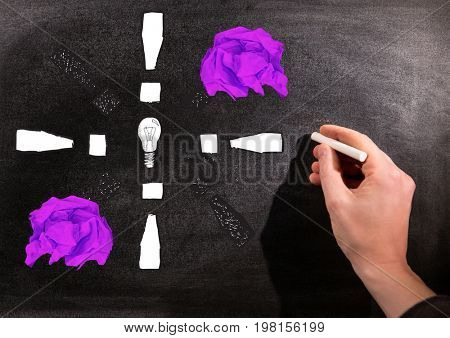 Digital composite of Hand drawing light bulb with crumpled paper balls in front of blackboard