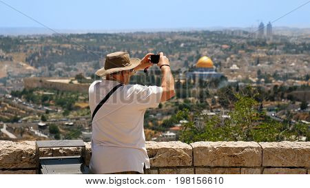 Tourist takes a photo of Jerusalem Old City view. Mount Scopus is a famous Holy Land place and it has a fantastic view to the Old Jerusalem. Jerusalem is a beautiful and popular touristic city.