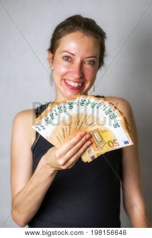 Happy wo man with a lot of 50 euro banknotes. Gold-digger girl
