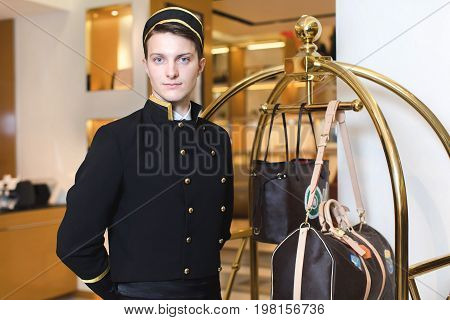 Smiling man in bellboy uniform standing with luggage cart and looking at the camera