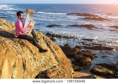 Musician play Tuba musical instrument on sea shore outdoor.