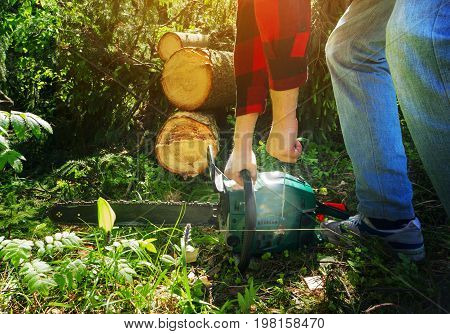 The logger in a red checkered shirt is holding an chainsaw is going to start it against the forest