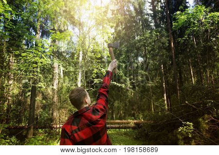 The logger in a red checkered shirt is holding an ax against the forest