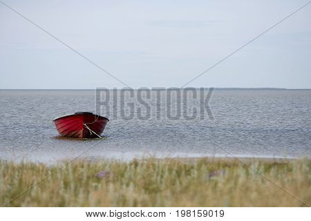 Red fishing boat in the bay at Bloeden Hale Laesoe Island in Kattegat sea Denmark.