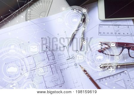 The architects 'and engineers' desks are full of working equipment such as blueprints, pens, pencil, glasses, mobile phones with icon diagram.
