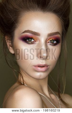 Close up portrait of beautiful young woman with professional makeup, perfect skin, volume hairdo. Trendy colorful smoky eyes.