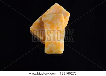 Slices Of Marble Cheese Isolated On Black Background