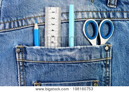 Engineers tools with denim fabric. Engineering and design concept. Things for drawing in back pocket of male denim pants close up. Metal scissors ruler blue pen and pencil in jeans pocket.