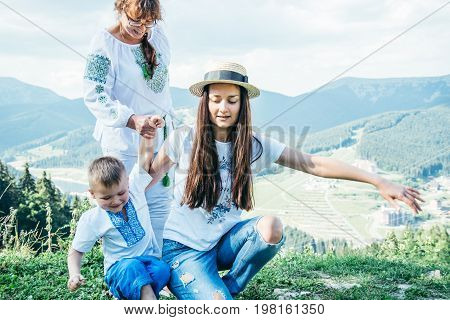 mother, son and grandmother climbing in mountains on vocation