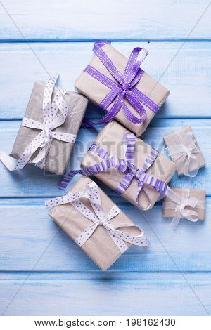 Different festive gift boxes with presents on blue wooden background. Selective focus.