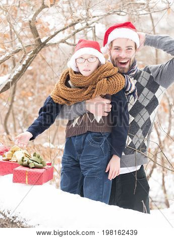 small smiling boy in glasses santa claus hat and knitted scarf and handsome man or bearded father guy holds red christmas or new year present boxes in winter outdoor with snow on natural background