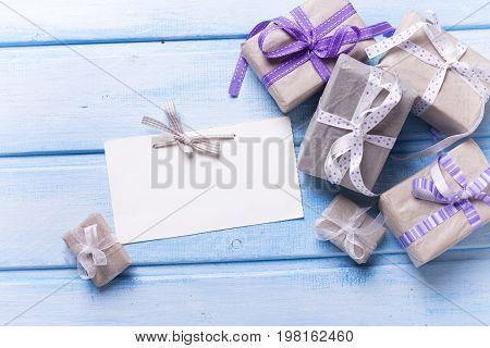 Gift boxes with presents and empty tag on blue wooden background. Selective focus. Place for text. Top view.