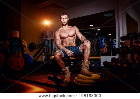 Bodybuilder Sits On A Weight Bench, He Takes A Break. Muscular Man At A Workout Place In A Gym And S