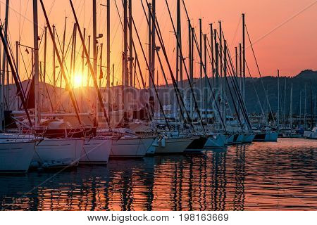 Sailboats in the harbor in mild sunset light, beautiful view on the luxury water transport in the dock, summer vacation in Marmaris, Turkey