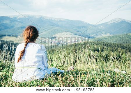 mature woman sitting on the peak of the hill and enjoing the view, warm sunny day