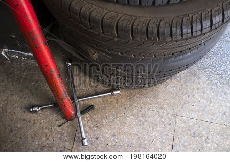 Used tyres with Fixed Cross Wheel Wrench. Changing car tire concept