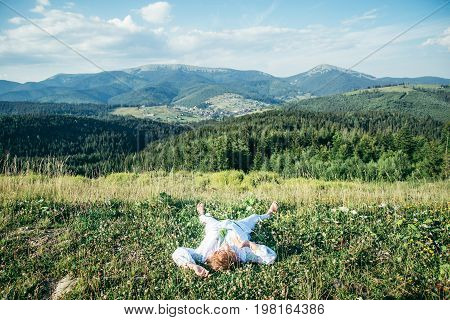 mature woman lying on the peak of the hill and enjoing the view, warm sunny day