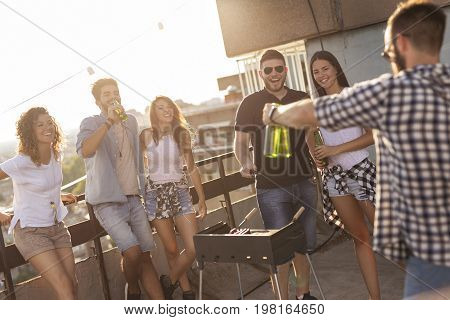 Group of young friends having fun at rooftop party making barbecue drinking beer and enjoying hot summer days. Focus on the couple on the right