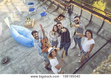 Top view of a group of young friends having fun at a rooftop party playing the guitar singing and enjoying hot summer days. Focus on the people in the middle