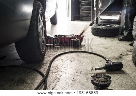 Mechanic rising a van. He is using a jack for tire change. Motion blurred