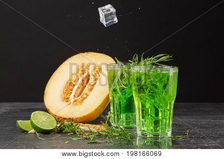 Two huge glasses of green alcoholic drink with ice cubes, tarragon leaves and near a half of a melon on a black background. Refreshing summer beverages with a cut melon and cut lime. Summer cocktails.