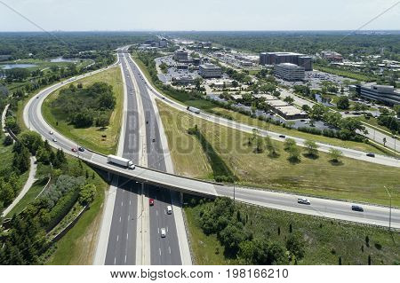 Aerial view of a highway and ramp with cars and trucks in a Chicago suburban setting.