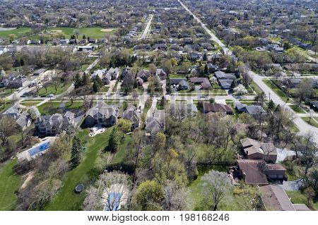 Aerial view of a neighborhood in suburban Chicagoland with homes, parks, baseball diamonds and swimming pools.
