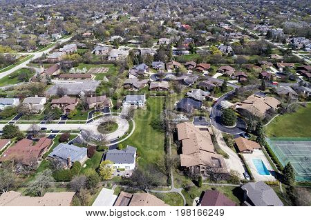 Aerial view of a neighborhood in the suburban Chicago area with homes, cul-de-sac; parks, tennis courts and swimming pools.