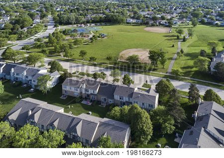 Aerial view of a neighborhood community in a Chicago suburban setting with a playground, park, tennis courts and baseball field.