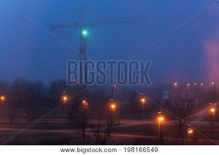 Tower crane and illumination at night, construction site.