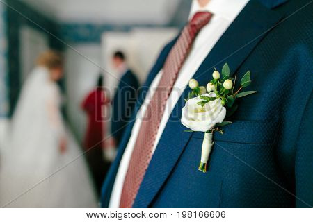 White boutonniere pinned to a grooms jacket. Wedding preparation. Close-up