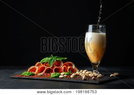 A tall and huge glass filled with golden cold beer and salted pistachios, cut twisted pieces of prosciutto on a black background. Copy space. Pistachios and a plate of sliced balyk pieces.