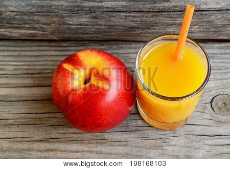 Fresh ripe organic nectarine and a glass of juice on old wooden table.Nectarine juice.Peach juice.Diet,healthy food,raw food concept.Selective focus.