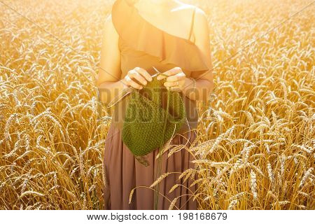 Beautiful slender woman in a romantic light top and wide skirt knits a sweater from green natural woolen threads standing in a field of wheat on a beautiful summer day the sun shines brightly