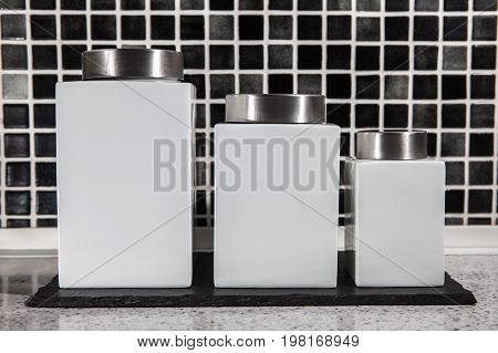 Square white storage jars in modern black and white tiled kitchen. Ceramic containers with label space.