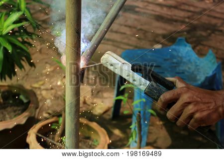 Worker with electric welding portable machine in the garden.