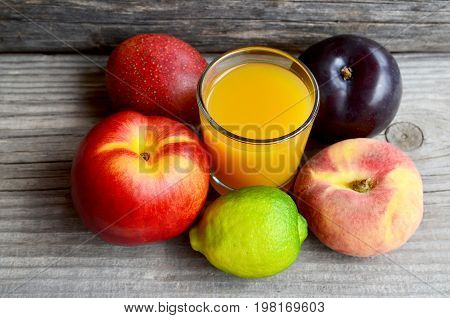 Fresh ripe fruits and a glass of juice.Multi fruit juice.Juice mix fruit on old wooden table.Healthy drink or diet concept.Selective focus.