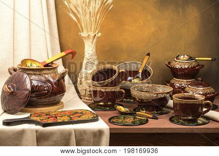 Clay pot for cooking with cups mugs and a vase with ears on the table with a background