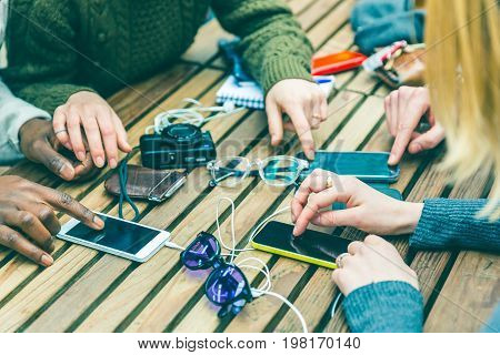 Friends Using Phones On The Table