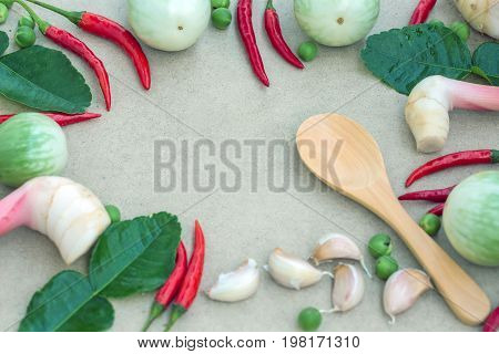 Eggplant, Daffie lime, red pepper, garlic, and spoon are made of wood, placed around a white board, with no space in the middle for additional items.